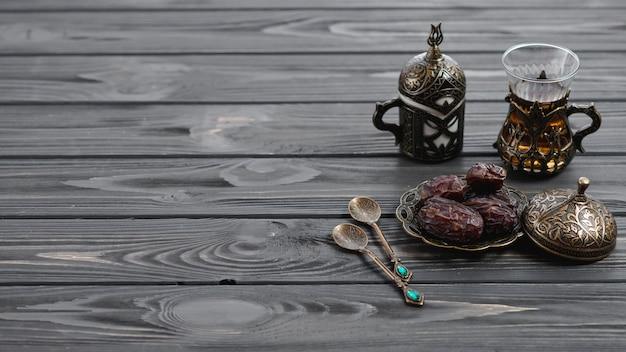 Verres à thé arabes turcs traditionnels et dates séchées avec des cuillères sur une table en bois Photo gratuit
