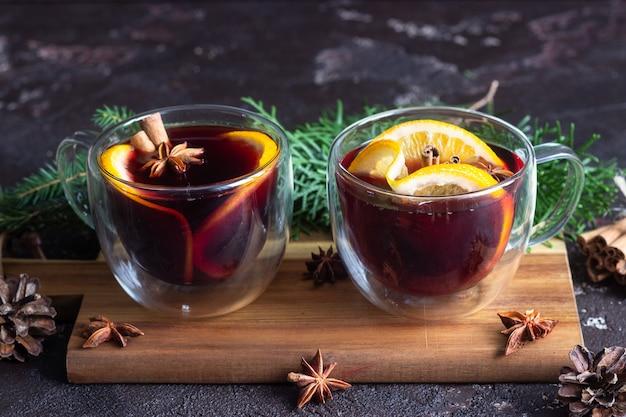 Verres de verre de vin chaud chaud ou gluhwein avec des épices et des morceaux d'orange. Photo Premium