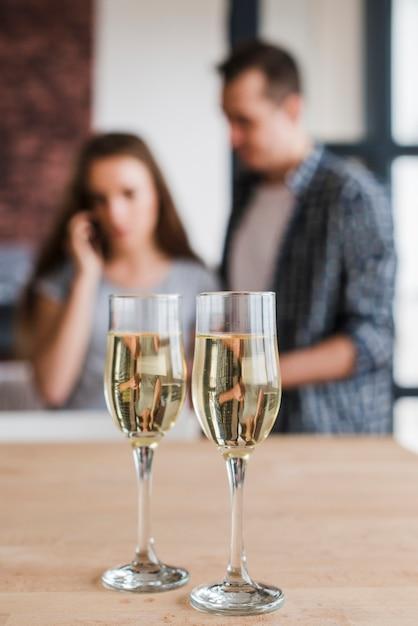 Verres à vin blanc et couple à la maison Photo gratuit