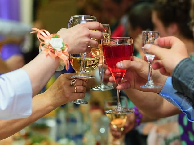 Verres de vin dans les mains d'amis célébrant les vacances Photo Premium
