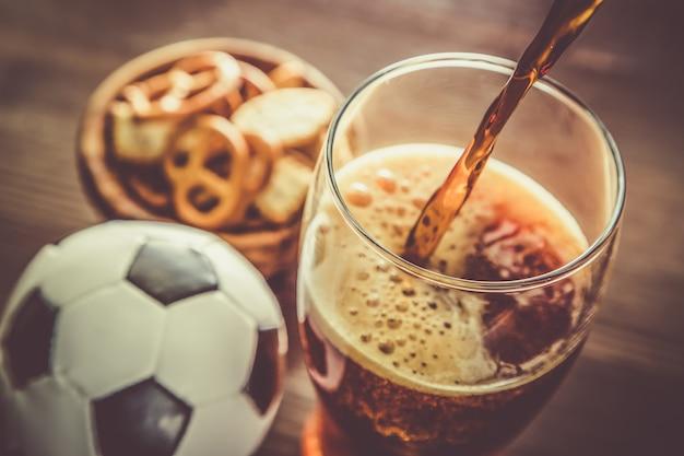 Verser de la bière dans un verre avec des collations et du football Photo Premium