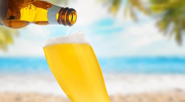 Verser La Bière Dans Un Verre Sur La Plage De La Mer Photo Premium