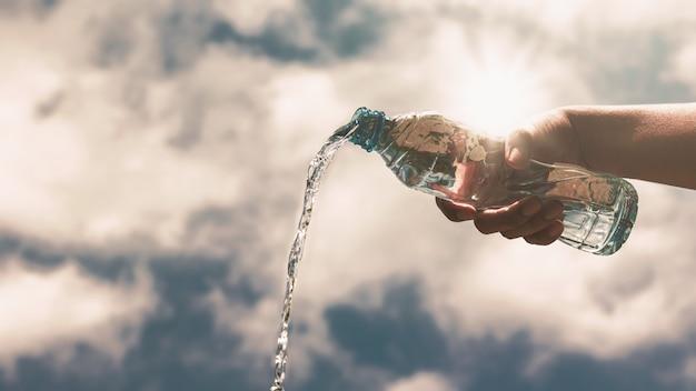 Verser une bouteille en plastique transparent d'eau potable pure rafraîchissante et éclabousser. Photo Premium