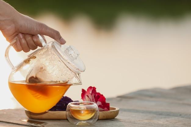 Verser du thé chaud dans le verre Photo gratuit
