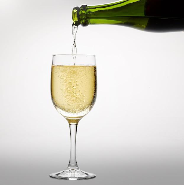 Verser du vin blanc pétillant dans un verre à vin Photo Premium