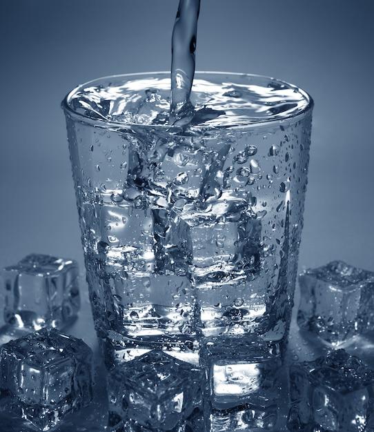 Verser de l'eau boire dans un verre avec un glaçon Photo Premium