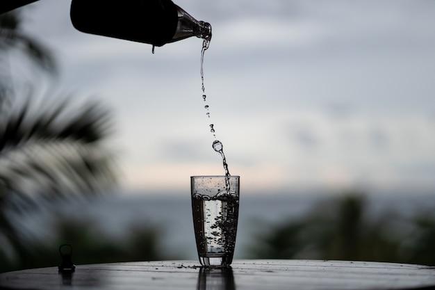 Verser de l'eau de la bouteille dans le verre sur fond de nature Photo Premium