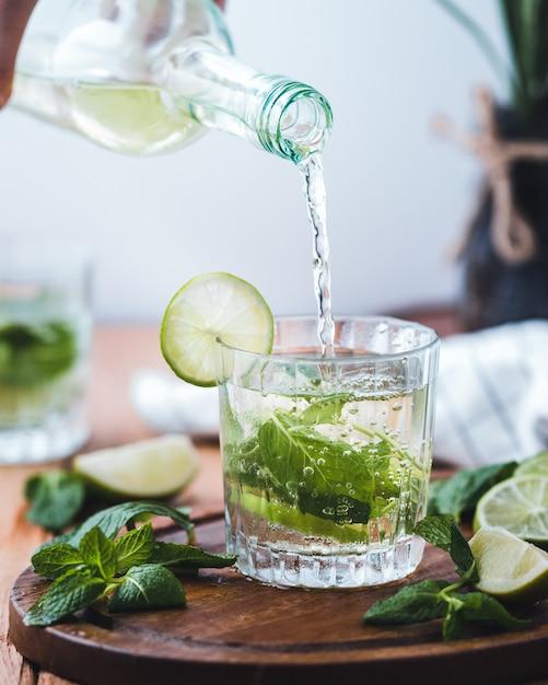 Verser de l'eau avec de la chaux dans une tasse en verre Photo gratuit