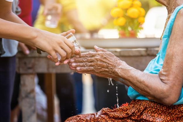 Verser de l'eau sur les mains des anciens vénérés et demander une bénédiction heureuse pour le festival de songkran Photo Premium