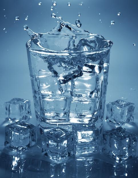 Verser un glaçon dans un verre d'eau. éclaboussures d'eau. Photo Premium