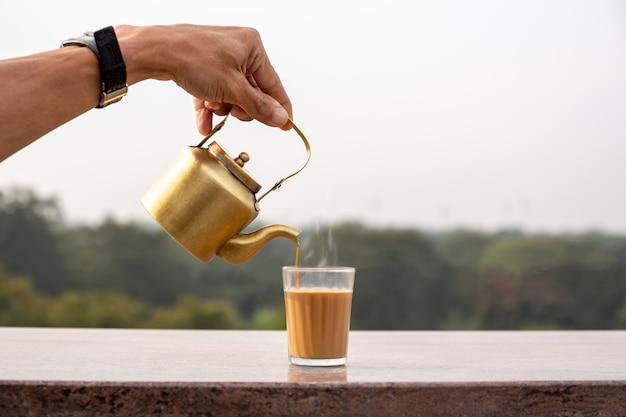 Verser à la main le thé masala de la théière dans un verre. Photo Premium