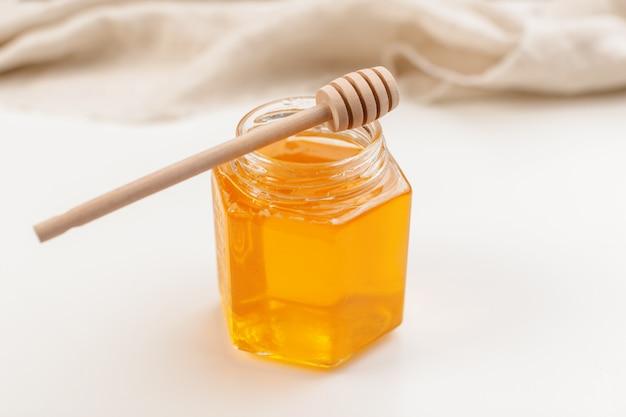 Verser le miel aromatique dans un bocal, gros plan Photo Premium
