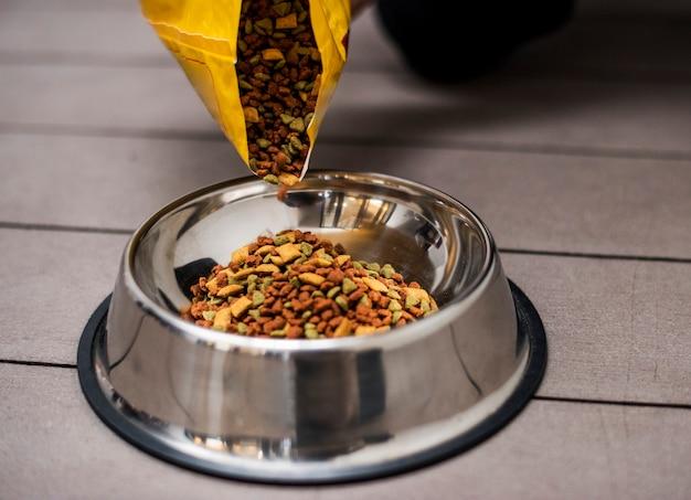 Verser de la nourriture pour animaux dans un bol Photo gratuit