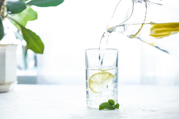 Verser un verre d'eau avec du citron, de la glace et de la menthe sur une table blanche Photo Premium