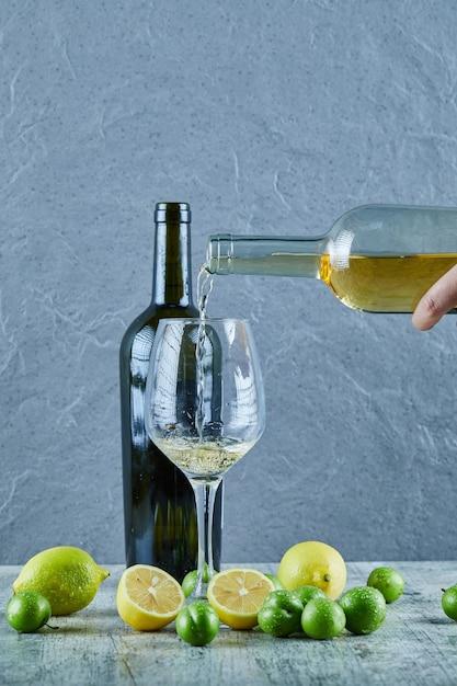 Verser Le Vin Blanc Dans Le Verre Et Les Citrons, Bouteille De Vin Et Prunes De Cerise De Côté Photo gratuit
