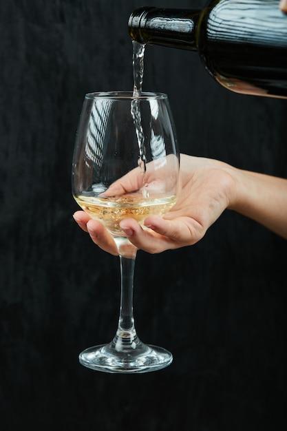 Verser Le Vin Blanc Dans Le Verre à Vin Sur Une Surface Sombre Photo gratuit
