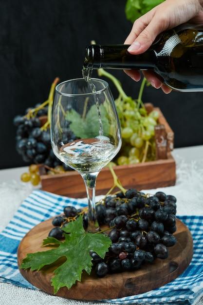 Verser Le Vin Dans Le Verre Avec Assiette De Raisins Sur Tableau Blanc Photo gratuit