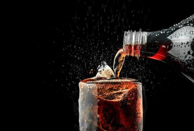Versez une boisson gazeuse dans un verre avec des éclaboussures de glace sur un fond sombre. Photo Premium