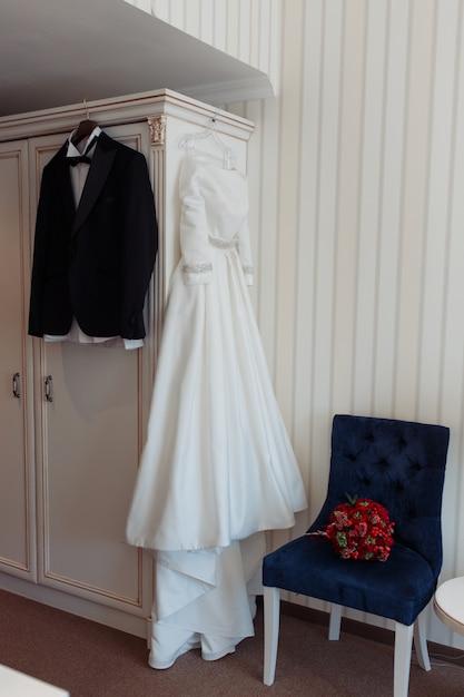 Veste et robe de mariée de la belle mariée noire suspendue dans la chambre d'hôtel Photo gratuit