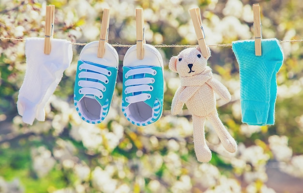 Les vêtements et les accessoires de bébé pèsent sur la corde après avoir été lavés à l'air libre. mise au point sélective. Photo Premium