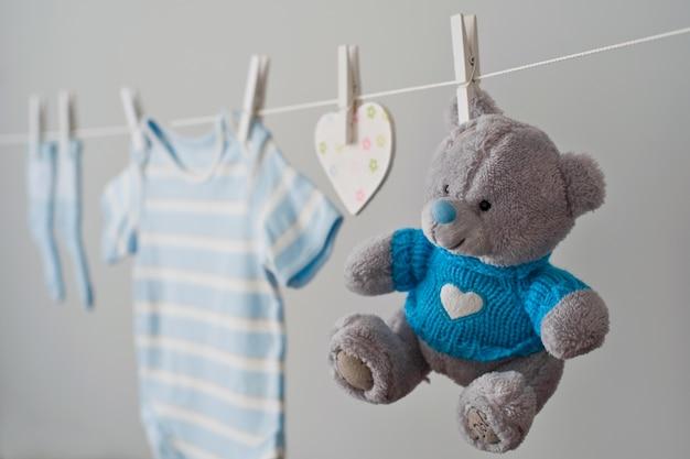 Vêtements de bébé bleu sur la corde à linge Photo Premium