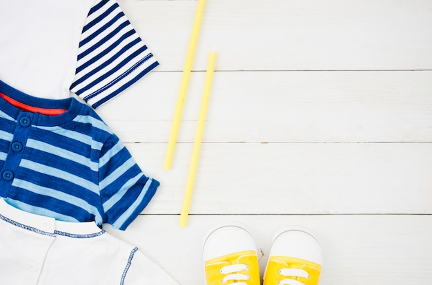 Vêtements bébé vue de dessus avec fond en bois Photo gratuit