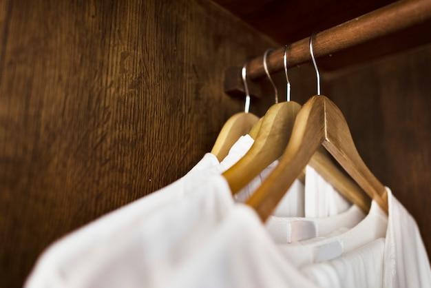Vêtements blancs suspendus dans une armoire Photo gratuit