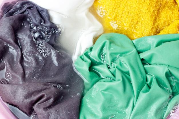 Vêtements colorés lavés avec une bassine avec des bulles de savon Photo Premium
