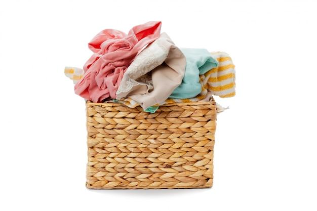 Vêtements dans un panier à linge en bois isolé sur blanc Photo Premium