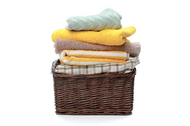 Vêtements dans un panier à linge en bois isolé sur fond blanc Photo Premium