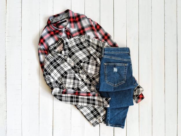 Vêtements . deux chemises à carreaux et des jeans sur un bois. vue de dessus Photo Premium