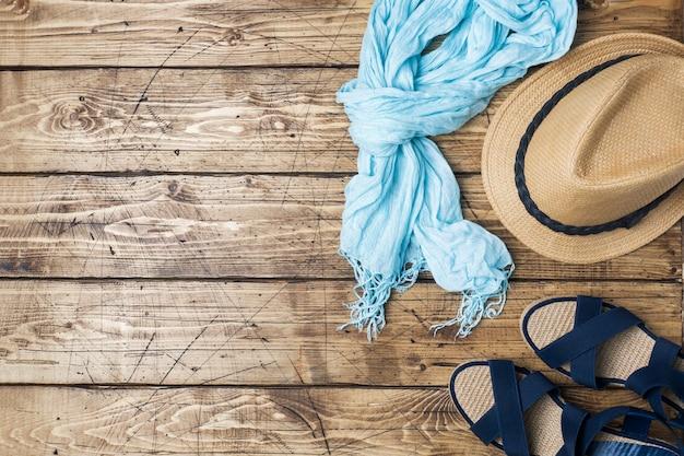 Vêtements d'été pour femmes. photo de mode plat laïque. écharpe et chapeau de soleil, sandales bleues sur fond en bois. espace de copie Photo Premium