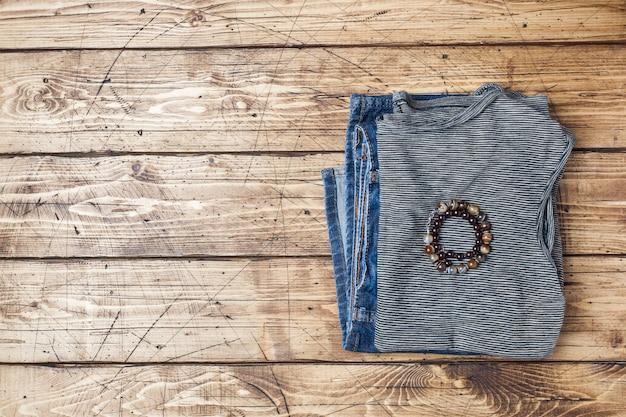 Vêtements d'été pour femmes. photo de mode plat laïque. t-shirt rayé gris et blue jeans sur fond en bois. Photo Premium