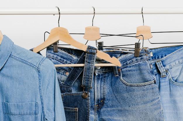 Vêtements en jean sur des cintres Photo gratuit