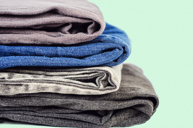 Vêtements à la mode, tas de jeans sur fond. Photo Premium