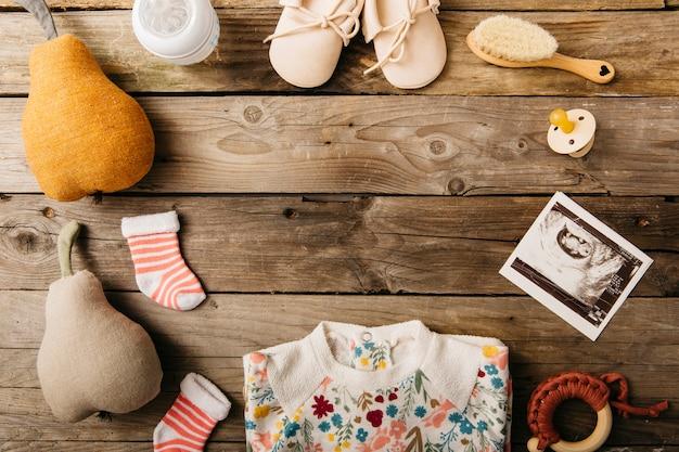 Vêtements et produits pour bébé disposés en forme circulaire sur une table en bois Photo gratuit