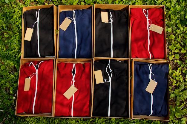 Des Vêtements De Sport Colorés Avec Des étiquettes Pliées Dans Des Boîtes En Carton Reposent Sur Le Sol Avec De L'herbe. Photo Premium