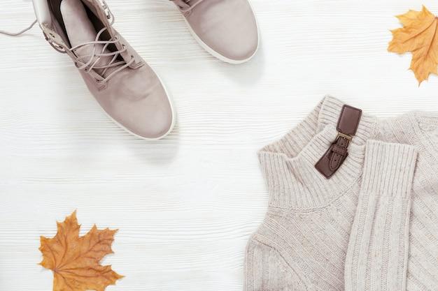Vêtements tout-aller pour femmes, climat d'automne, bottes en cuir à la mode, pull chaud en tricot. pose à plat avec des vêtements confortables sur un bureau en bois blanc. concept de présentation de shopping. Photo Premium