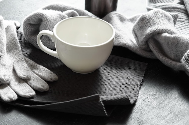 Vêtements Tricotés Et Tasses à Café Sur Une Surface Noire Photo Premium