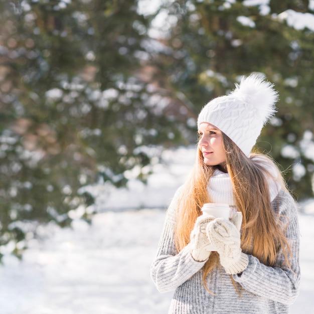 Vétérinaire tenant une tasse de café à emporter debout en hiver Photo gratuit