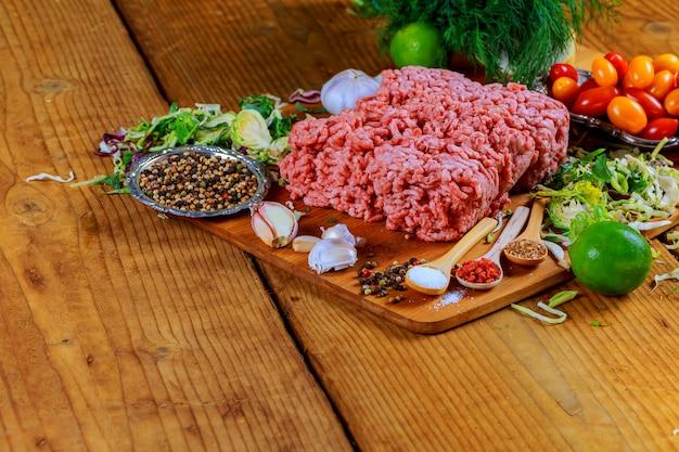 Viande de boeuf hachée crue côtelettes de bifteck avec assaisonnement, tomates, Photo Premium