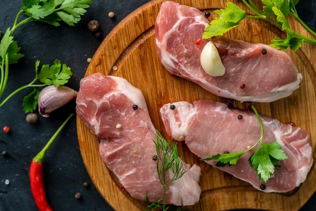 De la viande crue épicée sur une planche à découper en bois ou à découper, mettez du sel sur une viande non cuite Photo Premium