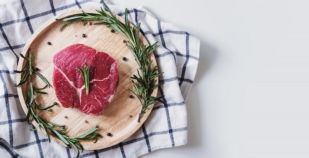 Viande Crue, Steak De Boeuf, Sur Planche De Bois Au Romarin Photo Premium