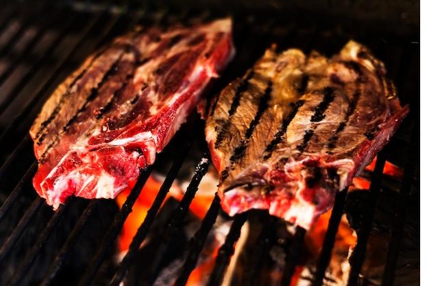 Viande grillée sur la flamme chaude au barbecue Photo gratuit