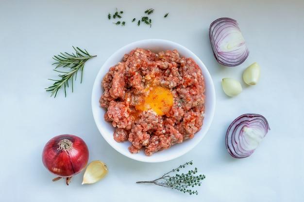 Viande hachée crue avec du poivre, des œufs, des herbes et des épices pour la cuisson d'escalopes, de hamburgers et de boulettes de viande. concept-cuisine, recettes, plats délicieux. Photo Premium