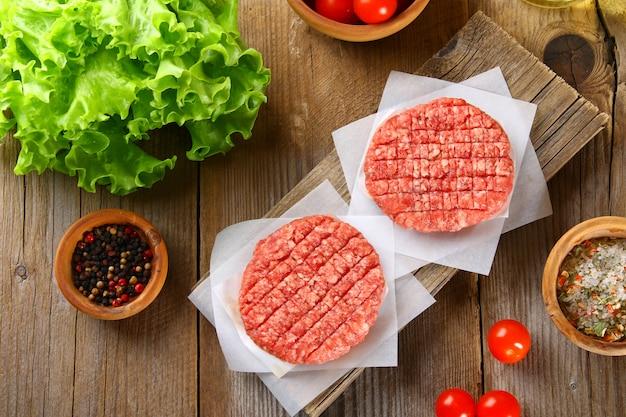 Viande hachée crue pour les hamburgers grillés faits maison cuisant avec des espaces et des herbes. Photo Premium