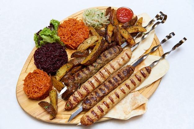 Viande et légumes sur une planche de bois. Photo Premium