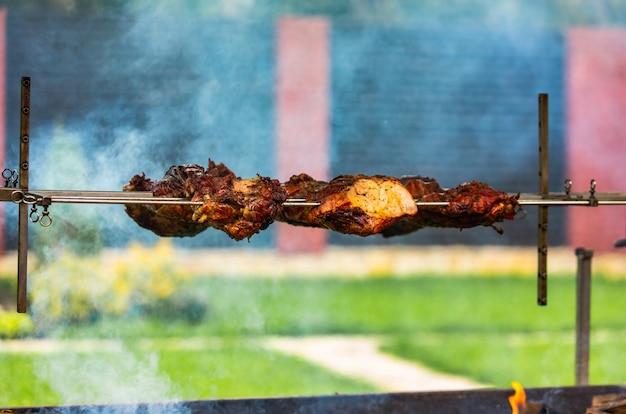 La viande de porc se prépare sur une brochette sur le feu dans la cour en été. la fumée donne du piquant à la viande Photo Premium