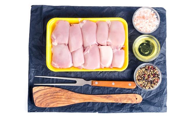 Viande de poulet crue dans un plateau jaune. Photo Premium