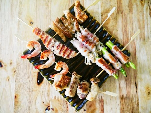 Viande de poulet frit et barbecue aux fruits de mer avec des légumes sur des brochettes de bois sur une sauce à la planche. vue de dessus Photo gratuit
